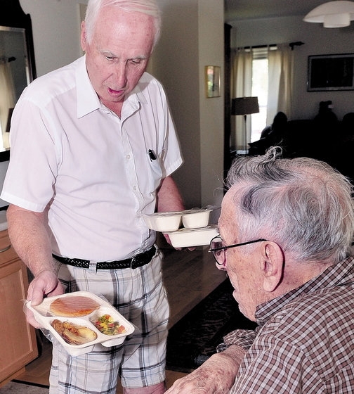 HELPING: Meals on Wheels driver Gil Pelletier, left, delivers food to Thaddy Gondela in Waterville in 2011. The program run by Spectum Generations is one of several area programs facing federal cuts, but helps prevents medical costs because volunteers might recognize a medical issue before it becomes a costly crisis.