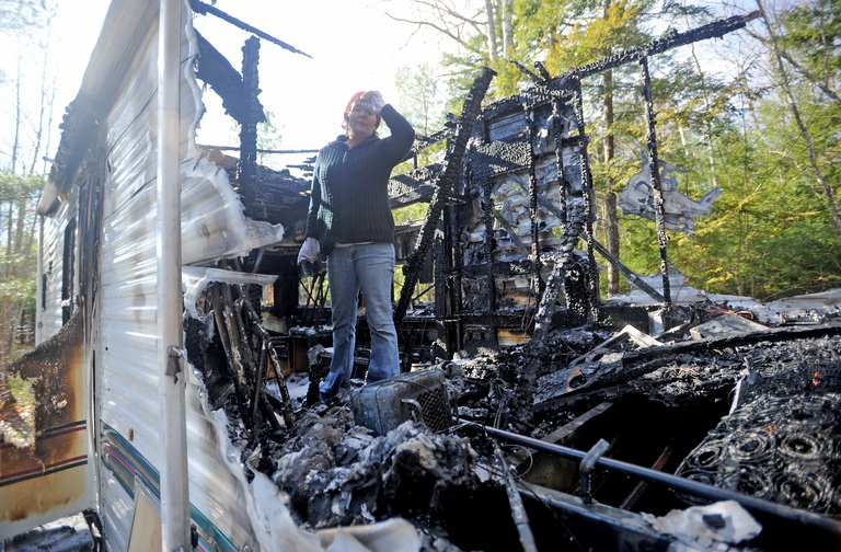 Burned: Laura Ellis investigates the damage to the camper trailer she was staying in on Beach Road in South China on Tuesday morning.