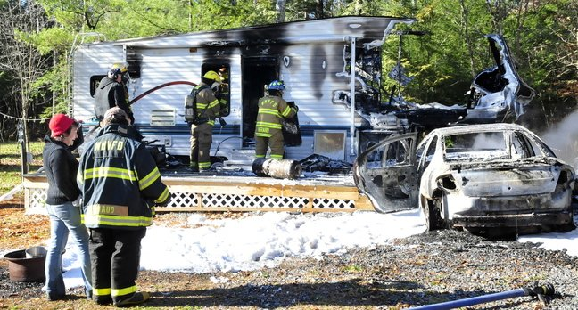 DESTROYED: Laura Ellis, left, speaks with a firefighter as others extinguish the destroyed remains of a camper she was staying in Tuesday on Beach Road in South China. Ellis was staying at friend and owner Tim Elkin's camper when she started her car, right, which caught fire, then ignited the camper.