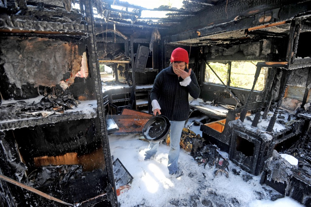 FIRE AFTERMATH: Laura Ellis investigates the damage to the camper trailer she was staying in on Beach Road in South China on Tuesday morning.