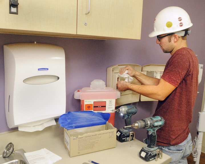 Aaron O'Neil wipes off dust from drilling in screws on Friday as he installs a sharps container at the Alfond Center for Health in Augusta. O'Neil and other H.P. Cummings employees were taking care of the last punch list items the day before the move.