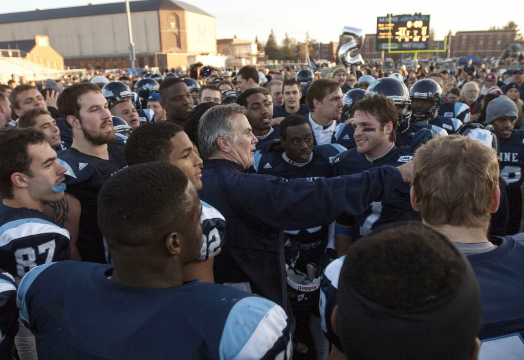 CELEBRATE: Maine football coach Jack Cosgrove, center, celebrates with his players after winning the regular season championship in the CAA with a 41-0 win over Rhode Island 41-0 Saturday in Orono.