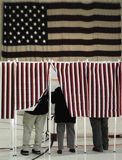 Voters fill in ballots in booths in front of a large American flag on Tuesday at Augusta's Ward 1 polling place in the Augusta Armory.