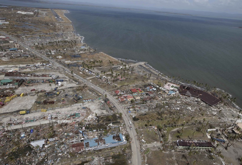 This aerial photo taken from a Philippine Air Force helicopter shows the devastation caused by Typhoon Haiyan in Tacloban city, Leyte province, central Philippines, Monday, Nov. 11, 2013. Typhoon-ravaged Philippine islands faced an unimaginably huge recovery effort that had barely begun Monday, as bloated bodies lay uncollected and uncounted in the streets and survivors pleaded for food, water and medicine. (AP Photo/Bullit Marquez)