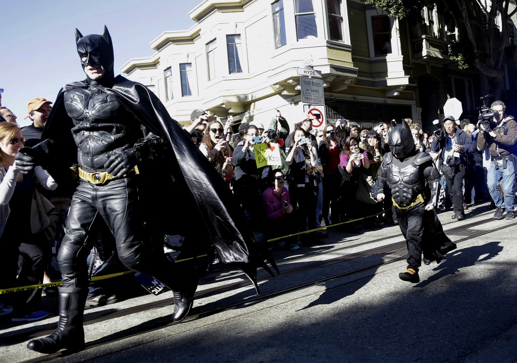 Miles Scott, dressed as Batkid, runs with Batman after saving a damsel in distress.