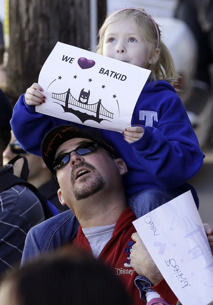 Daniel Fry holds up his daughter Kayla, 5, as they wait for Miles Scott, dressed as Batkid, in San Francisco.