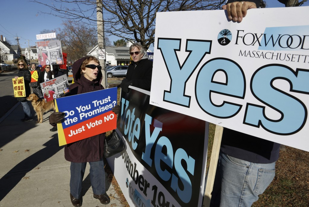 Barbara Morganelli, of Milford, Mass., center left, displays a placard while speaking with Chris Murphy, hand only at right, outside a polling place Tuesday, Nov. 19, 2013, in Milford.