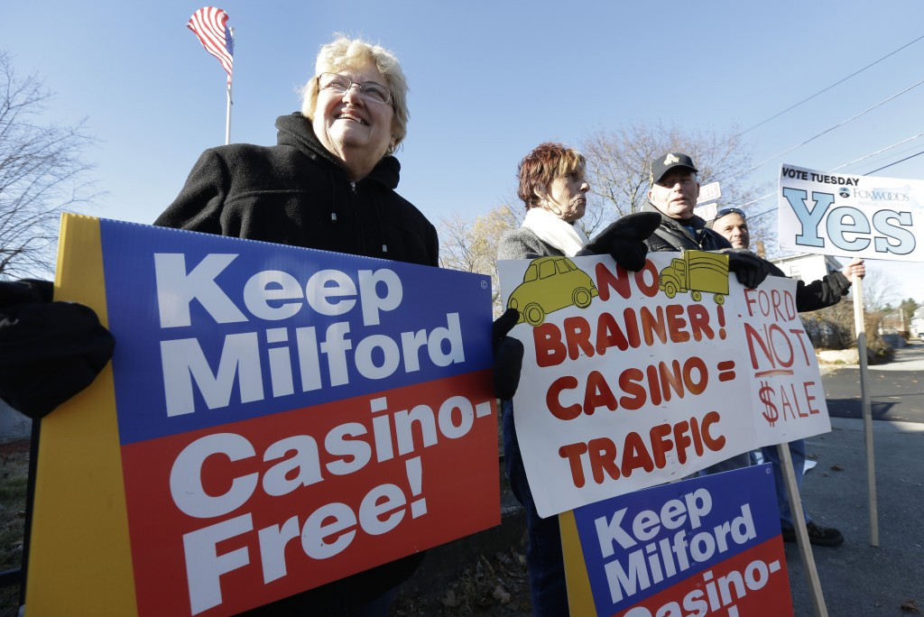 Mary Castrucci, left, and Rosemary Trettel, center, both of Milford, Mass., display placards outside a polling place Tuesday, Nov. 19, 2013, in Milford. The town's residents were deciding whether to put out the welcome mat for a proposed $1 billion resort casino that would have been built off Interstate 495.