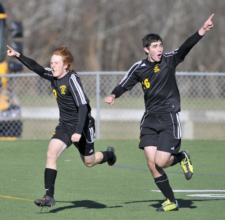 Staff photo by Michael G. Seamans Maranacook High School's Alex Tooth, 9, right, celebrates his first half goal against Madawaska with teammate Tyler Lang, 16, right, in the Class C State Championship game at Hampden Academy on Saturday. Maranacook defatted Madawaska 2-0.