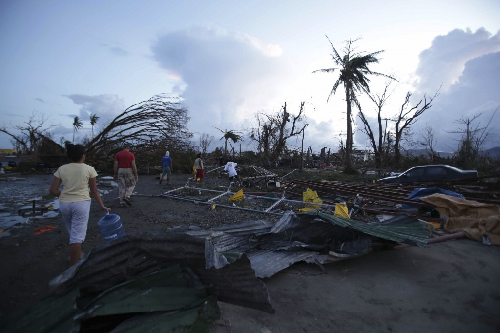 """Residents walk by debris after powerful Typhoon Haiyan slammed into Tacloban city, Leyte province, central Philippines on Saturday, Nov. 9, 2013. The central Philippine city of Tacloban was in ruins Saturday, a day after being ravaged by one of the strongest typhoons on record, as horrified residents spoke of storm surges as high as trees and authorities said they were expecting a """"very high number of fatalities."""""""