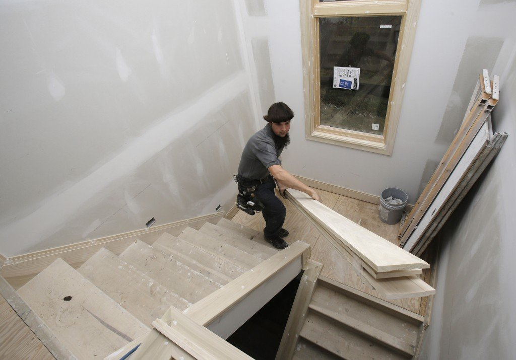 Will Hostetler, a carpenter with Larry Block Builders, carries trim downstairs at a new residential building under construction, in Pepper Pike, Ohio. Construction of single-family homes could slow in the coming months, but construction of apartments has increased.