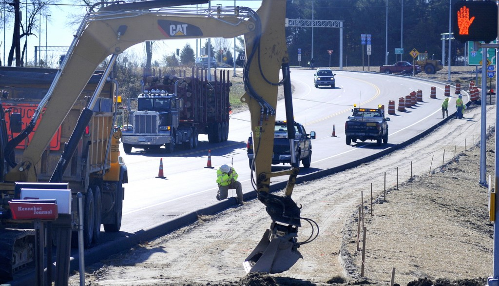 EXIT: Maine Department of Transportation engineer Matt Swindells stakes a sidewalk Monday near the entrance to the MaineGeneral Medical Center's new hospital in Augusta.