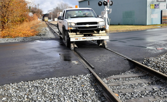 GENTLE CROSSING: A specially equipped truck rides on top of the rails of the Pan Am Railway over the recently improved crossing on Summit Street in Fairfield on Monday.