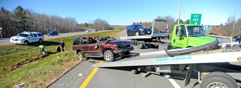 Clean-up: Officials pick up debris as two cars involved in a roll-over accident are loaded onto trucks at the scene of two-car accident on southbound Interstate 95 in Palmyra on Monday.