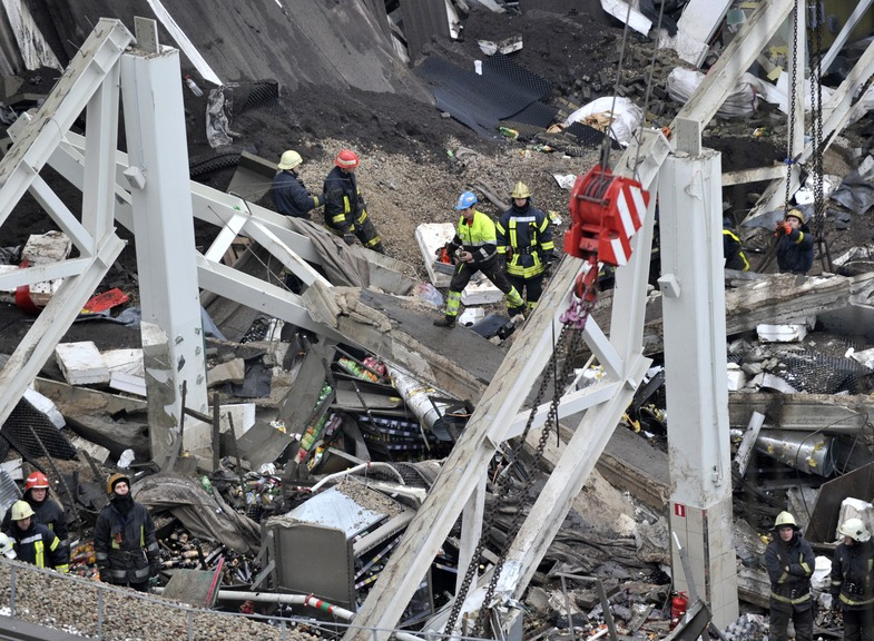 Rescue workers search debris of the Maxima supermarket in Riga, Latvia, Friday. At least 32 people died, including three firefighters, after a section of roof collapsed at a Latvian supermarket in the country's capital, emergency medical officials said.