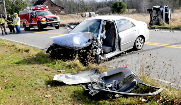 IMPACT: Cornville firefighters wait for police reconstruction investigators at the scene of a two-vehicle accident on Route 43 in Cornville on Tuesday. The drivers of both vehicles were injured and taken to the hospital.