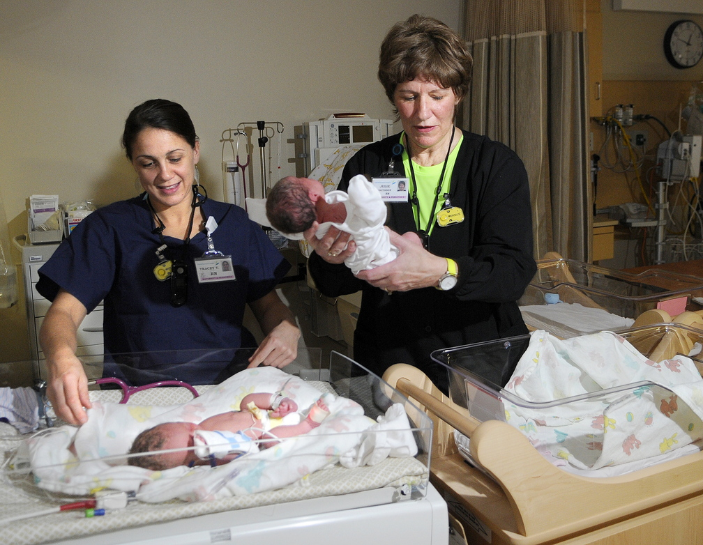 DELIVERING: Nurse Julie Smithson, right, lifts day old infant Hannah Veilleux away from her twin, Samuel, attended by nurse Tracey Thornton, at MaineGeneral's new neonatal intensive care unit in Augusta on Sunday. The siblings, born five weeks early, were the first babies born at the new hospital.