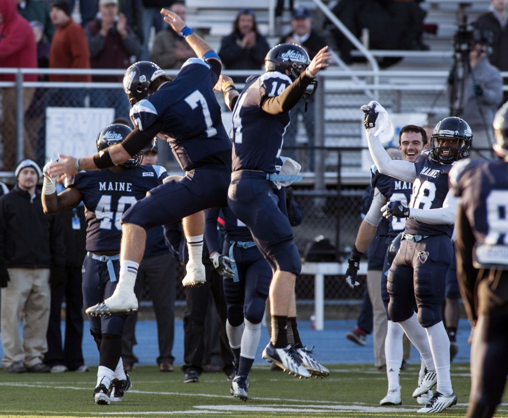 Maine quarterback Marcus Wasilewski (7) and teammate Daniel Collins (14) celebrate after defeating Rhode Island 41-0 in an NCAA football game in Orono, Maine, Saturday, Nov. 16, 2013. (AP Photo/Michael C. York)
