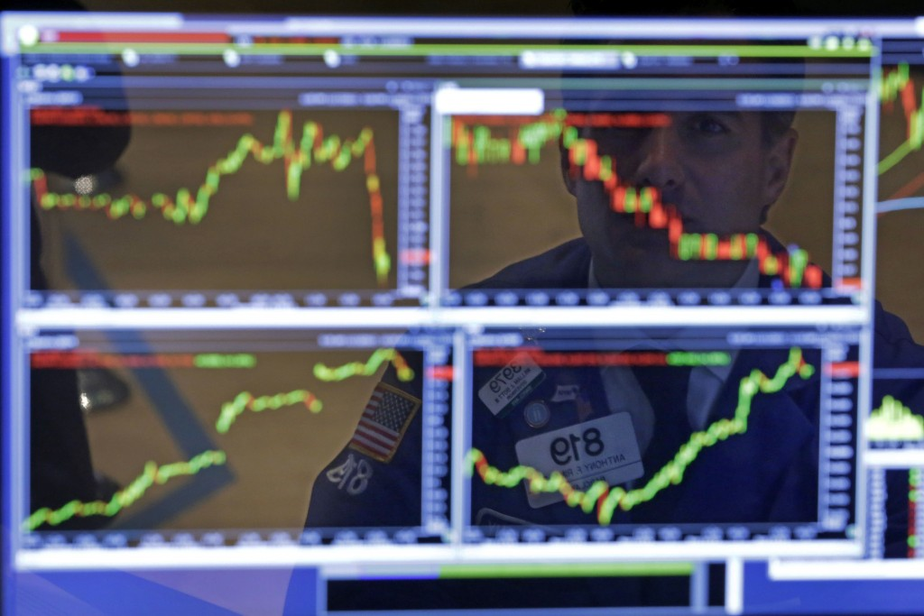 Specialist Anthony Rinaldi is reflected in one of his screens at his post on the floor of the New York Stock Exchange on Monday.