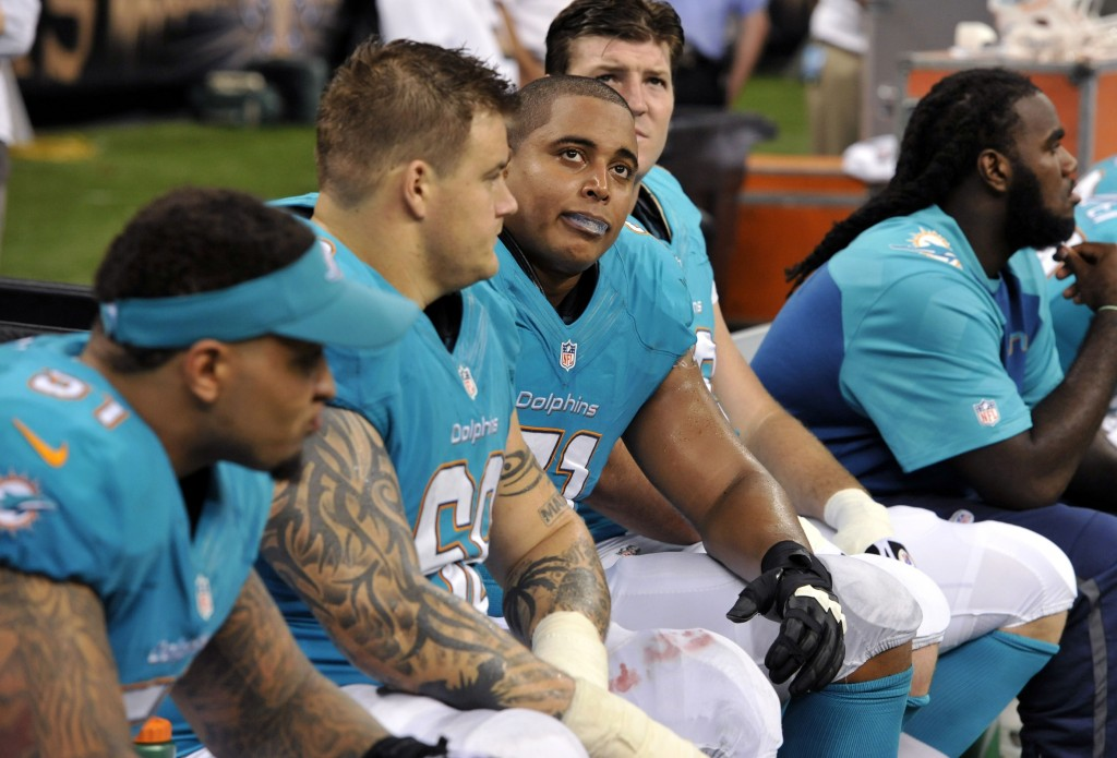 In this July 24, 2013 file photo, Miami Dolphins guard Richie Incognito (68) and tackle Jonathan Martin (71) stand on the field during an NFL football practice in Davie, Fla. Two people familiar with the situation say suspended Dolphins guard Incognito sent text messages to teammate Jonathan Martin that were racist and threatening. The people spoke to The Associated Press on condition of anonymity because the Dolphins and NFL haven't disclosed the nature of the misconduct that led to Incognito's suspension. Martin remained absent from practice Monday, Nov. 4, 2013, one week after he suddenly left the team.
