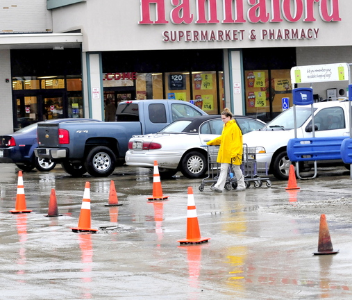 BOILED: A Hannaford employee gathers shopping carts Thursday at Elm Plaza in Waterville near a sectioned-off area where workers repaired an underground water main break on Wednesday. The Kennebec Water District ordered customers there to boil drinking water.
