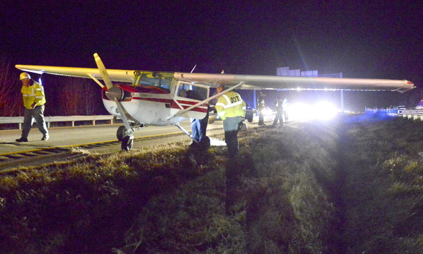 """State police and Maine DOT officials look over a small plane that made an emergency landing in the southbound lane of I-295 in Falmouth. """"It was amazing. He landed in the middle of the road. It was luck. I don't know any other way to put it,"""" a trooper said."""