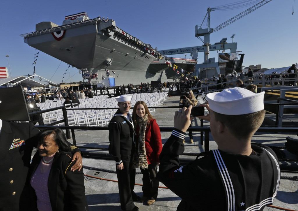 U.S. Navy Bosons mate, Ben Hansen and his wife Jessica, of Edmore Mich., are photographed in front of the Navy's newest nuclear powered aircraft carrier USS Gerald R. Ford for the christening of the ship at the Newport News Shipbuilding in Newport News, Va., Saturday, Nov. 9, 2013. Former President Ford's daughter Susan Ford Bales will christen the ship.)
