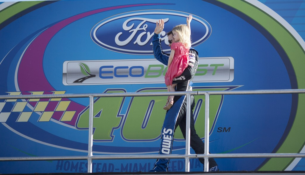 Jimmie Johnson holds his daughter, Genevieve, as he greets fans during driver introductions before the NASCAR Sprint Cub Series auto race in Homestead, Fla., Sunday, Nov. 17, 2013.