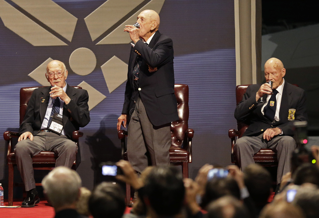 Richard Cole, center, proposes a toast with two other surviving members of the 1942 Tokyo raid led by Lt. Col. Jimmy Doolittle, Edward Saylor, left, and David Thatcher, Saturday, Nov. 9, 2013, at the National Museum for the US Air Force in Dayton, Ohio. The fourth surviving member, Robert Hite, was unable to travel to the ceremonies.