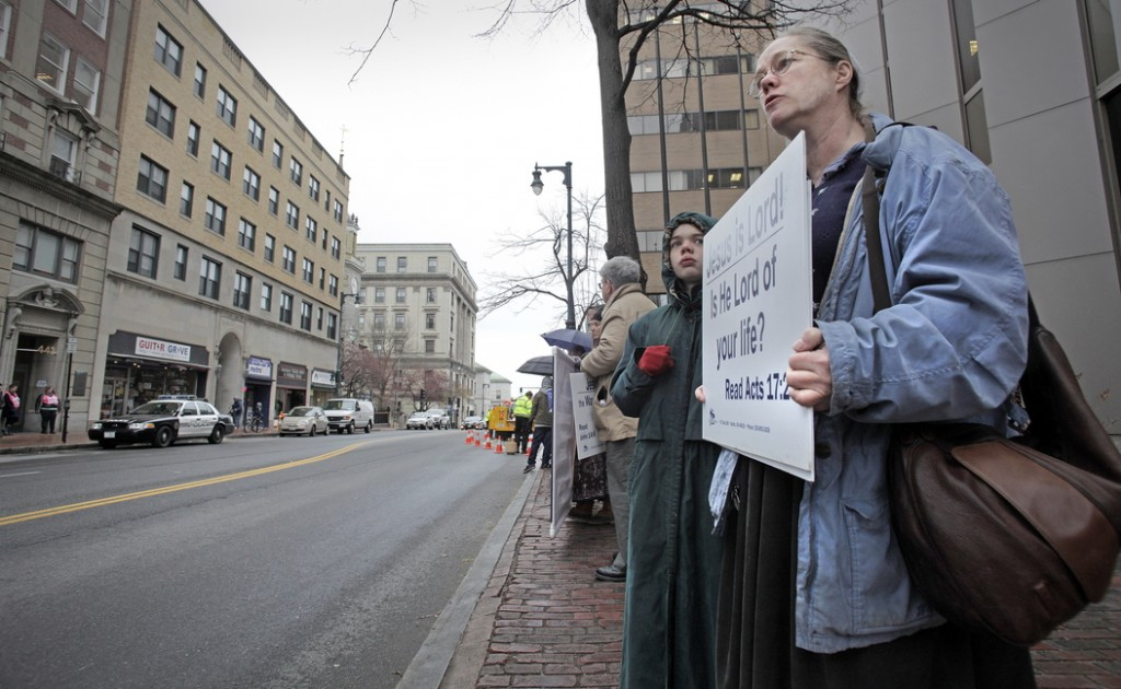 Marguerite Fitzgerald of Shapleigh stands with other anti-abortion protesters Friday across Congress Street from the Planned Parenthood clinic, where a Portland police car is parked. There is now a 39-foot buffer zone around the clinic.