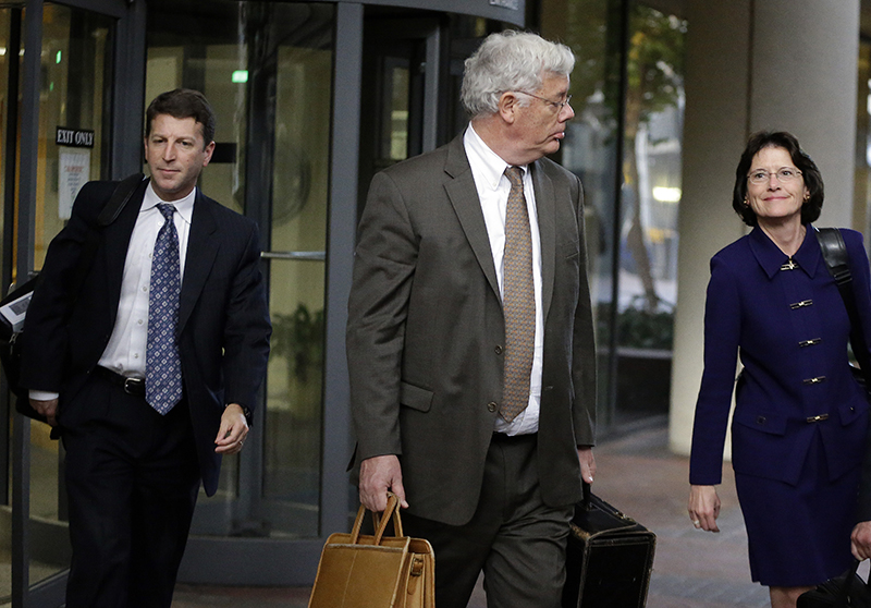 """Harold McIlhenny, center, an attorney representing Apple Computer in the Apple Samsung trial, exits a federal courthouse Wednesday, Nov. 13, 2013, in San Jose, Calif. How much does Samsung Electronics owe Apple for copying vital features of the iPhone and iPad, such as scrolling and the """"bounce-back"""" function at the end of documents? Apple says $380 million. Samsung counters with $52 million. The companies made their demands Wednesday during opening statements of a patent trial. At issue are 13 older products a previous jury found infringed several Apple patents. That previous jury awarded Apple $1.05 billion after determining 26 Samsung products had infringed six Apple patents."""