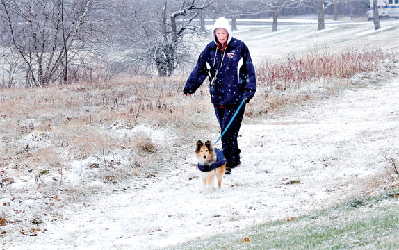 Staff photo by David Leaming WINTER WALK: Candice Hinckley and her dog Marx went for a walk on a snow covered trail in Waterville as snow fell most of the day on Sunday, Dec. 1, 2013.