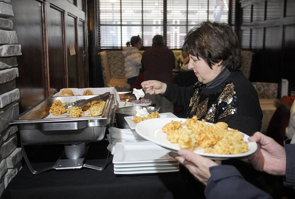 TIS THE SEASON: Susan Montell prepares a plate during the fifth annual latke festival at Alex Parkers Steakhouse in Gardiner on Sunday. The annual gathering open to the public celebrates the Jewish holiday of Hanukkah.