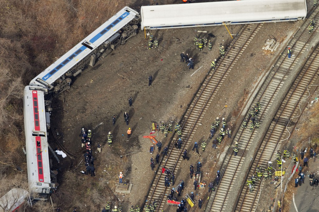 Emergency rescue personnel work the scene of a Metro-North passenger train derailment in the Bronx. The train derailed on a curved section of track on Sunday morning, coming to rest just inches from the water.