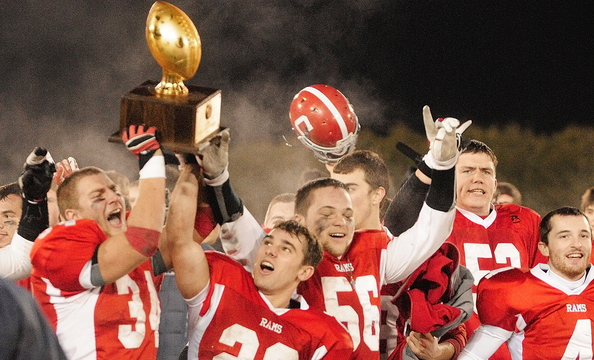 Long wait over: Members of the Cony High School varsity football team celebrate with a gold ball trophy after beating Kennebunk to win the state class B football championship game Nov. 22 in Orono.