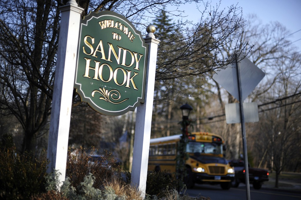 A bus drives past a sign reading Welcome to Sandy Hook, Wednesday, Dec. 4, 2013, in Newtown, Conn. The 911 calls from the Sandy Hook Elementary School shootings released Wednesday show town dispatchers urged panicked callers to take cover, mobilized help and asked about the welfare of the children as the boom of gunfire could be heard at times in the background. The recordings are released under court order after a legal challenge from The Associated Press.
