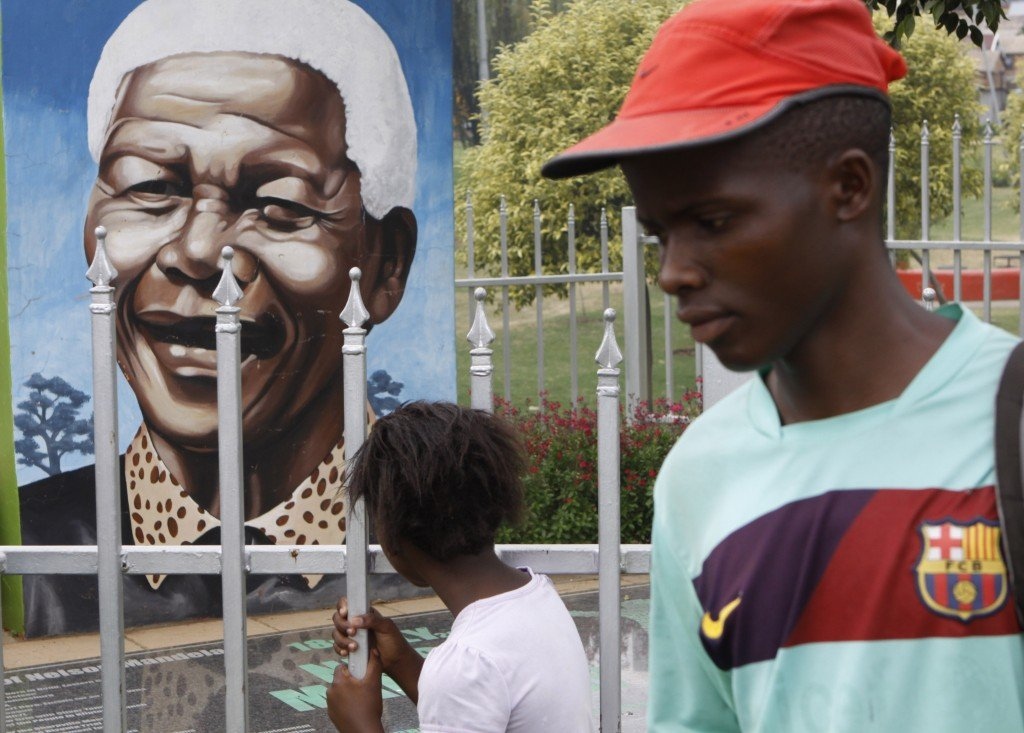 A child looks through a fence at a portrait of former President Nelson Mandela in a park in Soweto, South Africa, in this March 28, 2013 file photo. The Nobel laureate is a revered figure in South Africa, which has honored his legacy of reconciliation by naming buildings and other places after him and printing his image on national banknotes. On Thursday, Dec. 5, 2013, Mandela died at the age of 95.