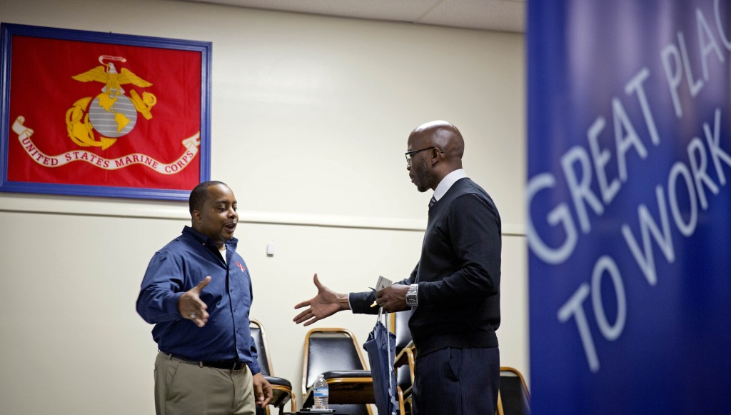 In this Thursday, Nov. 14, 2013 file photo, retired U.S. Army Sgt. 1st Class Duane Stubbs, right, of Morrow, Ga., shakes hands with retired U.S. Army 1st Sgt. Leland Smith, CEO of SolidHires, during a job fair for veterans at the VFW Post 2681, in Marietta, Ga. Solid job growth in November cut the U.S. unemployment rate to 7 percent, a five-year low. The surprisingly robust gain suggested that the economy may have begun to accelerate. As more employers step up hiring, more people have money to spend to drive the economy.