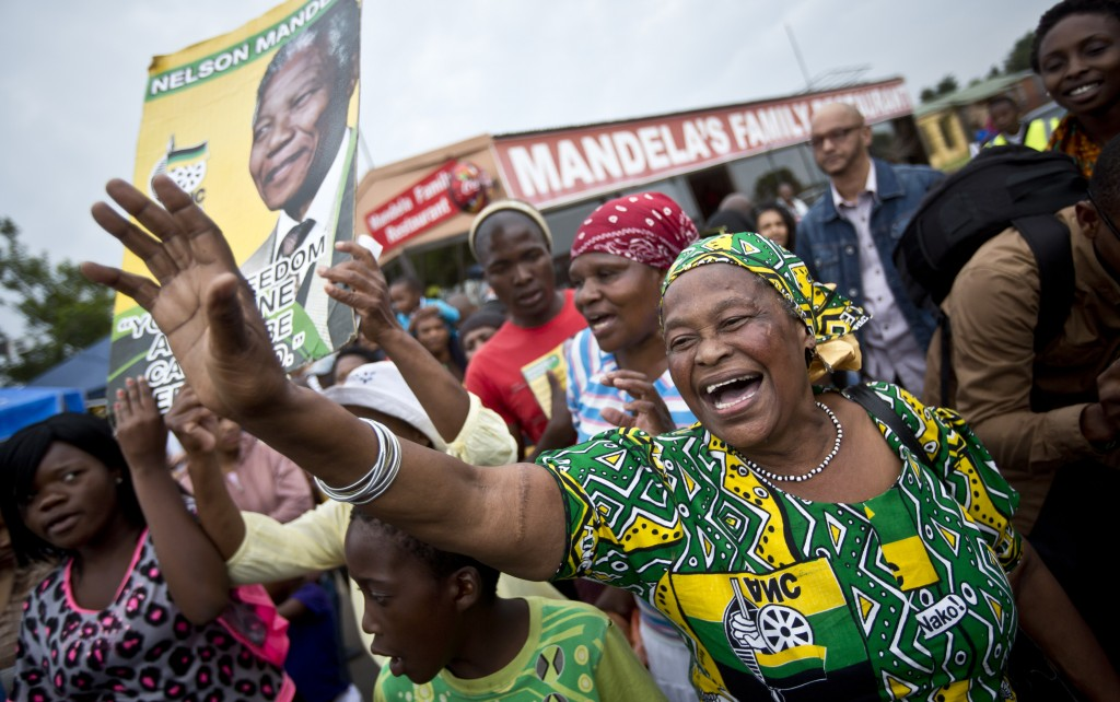 Mourners sing and dance to celebrate the life of Nelson Mandela in the street outside his old house in Soweto, Johannesburg, South Africa, on Friday. Flags were lowered to half-staff and people throughout the nation pledged to adhere to the values of unity and democracy that he embodied.
