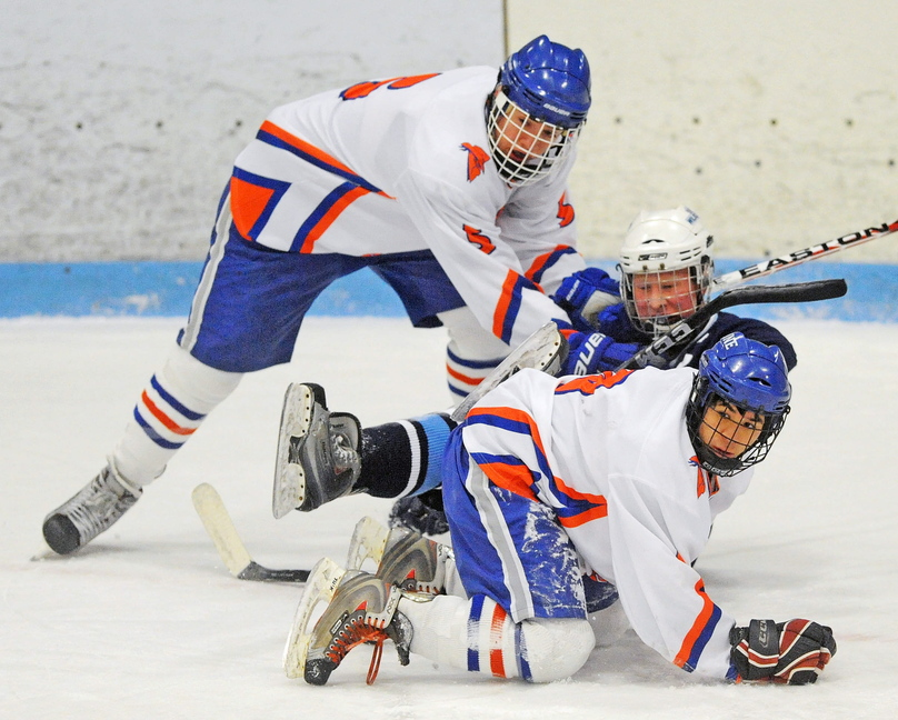 TIGHT QUARTERS: Lawrence/Skowhegan's Adam Littlefield, back, and teammate Anthony Paul (9) sandwich Presque Isle's Tyler Seely during the first period of their game Friday at Sukee Arena in Winslow.
