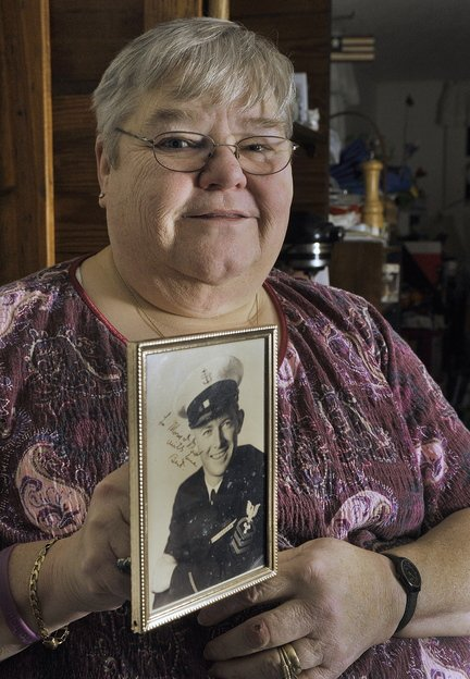 Jo Davis, above, holds a photograph of her late husband, Bert Davis, a Navy veteran who was at Pearl Harbor on Dec. 7, 1941.