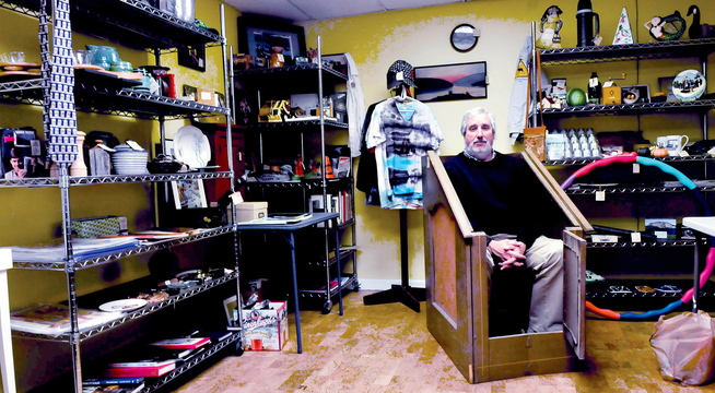 QUICK SALE: Iver Lofving sits inside an Anidrosis Box at his pop-up store in the Grist Mill in Skowhegan, where for two weeks he plans to sell a variety of unusual items. The box was used by locally by Dr. S.F. Conant in the 19th century. It is a sauna-like wooden crate used to help a person perspire. The person then was treated to a rubdown using an ointment of alcohol and opium to soothe ailments.