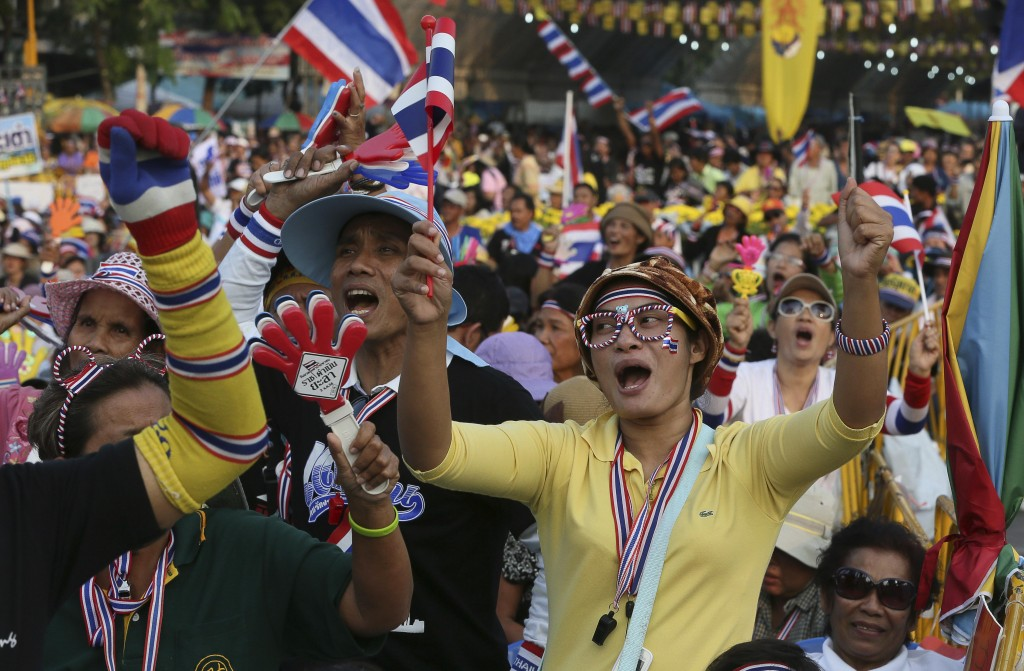 Anti-government protesters shout slogans at the Democracy Monument in Bangkok, Thailand, Sunday, Dec. 8, 2013.