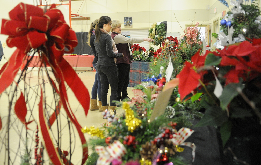 AUCTION ARRANGEMENTS: Val Dawes, right, plans the auction of floral arrangements Sunday with fellow volunteers Quinn Galletta, center, and Mair Guillemette at the Manchester Elementary School. The annual auction raises funds for winter home heating relief for Manchester residents.