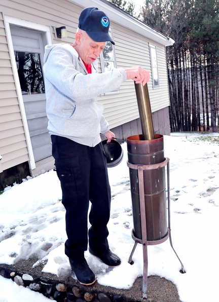 RECORD KEEPER: Dennis Pike sets up a precipitation collector at his home in Farmington where he records weather conditions for NOAA, National Oceanic Atmosheric Administration.