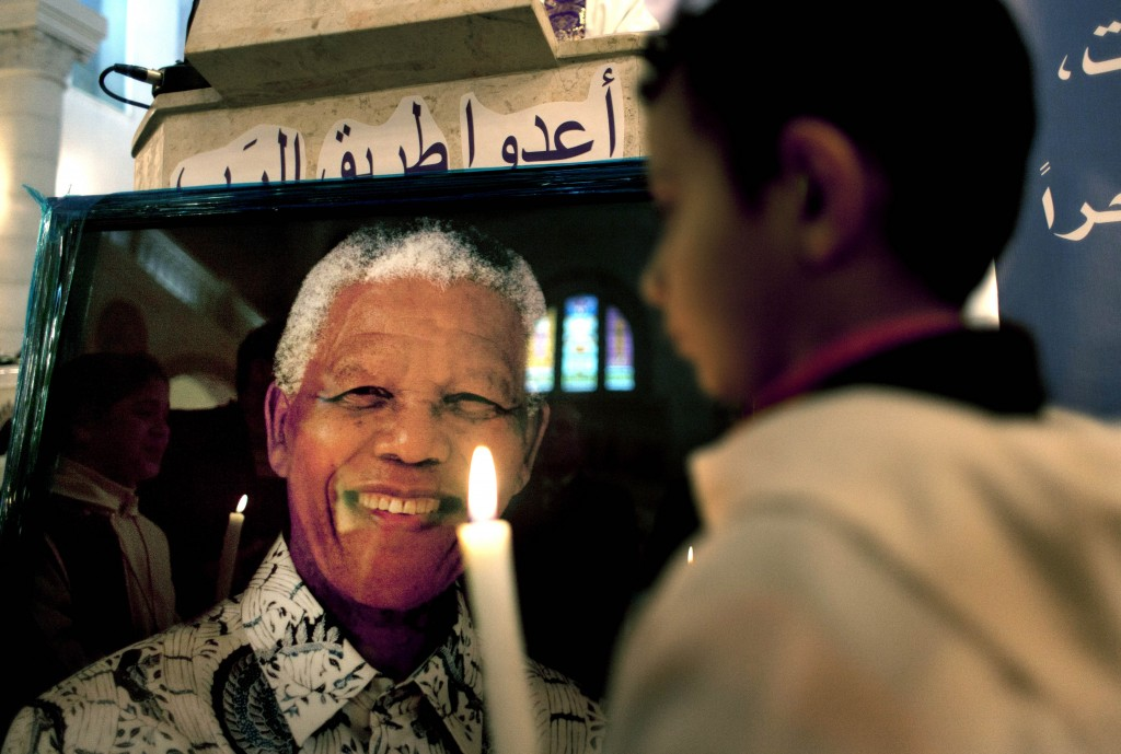 A Palestinian child holds a lit candle as he prays in front of a poster of late South African leader Nelson Mandela, during a special service in his honor at the Holy Family Church, in the West Bank city of Ramallah, on Sunday.
