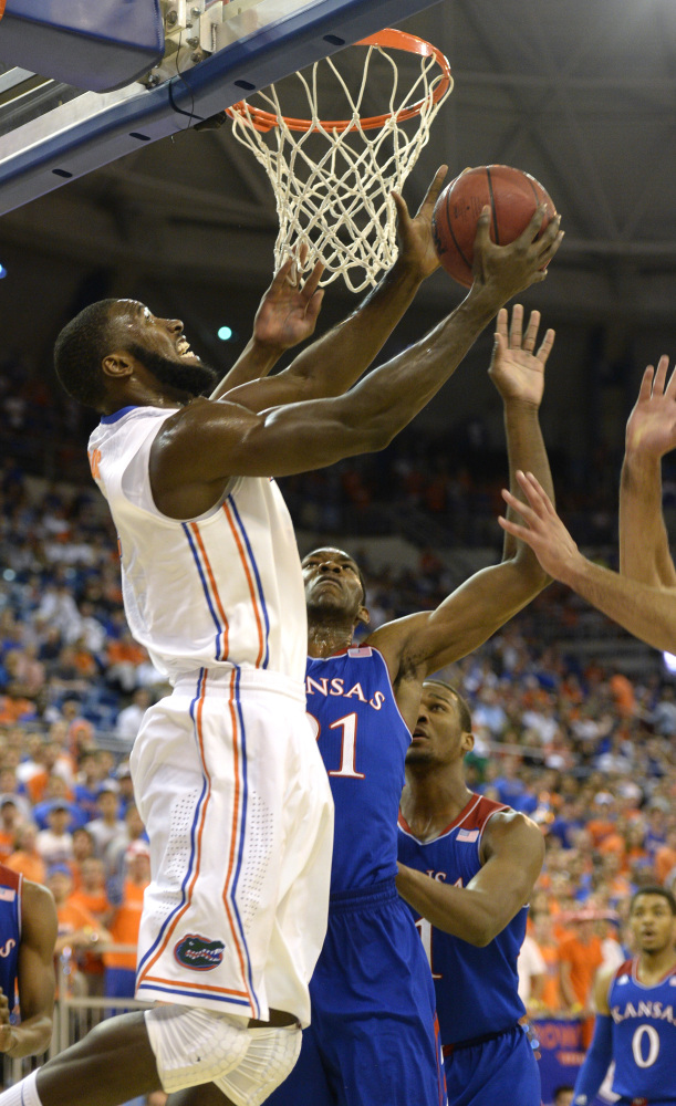 Florida's Patric Young evades the block of Joel Embiid during the first half of the Gators' 67-61 win over visiting Kansas Tuesday.