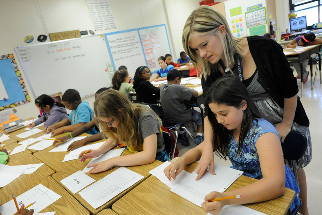 "Common core in classroom: Amy Lawson, a fifth-grade teacher at Silver Lake Elementary School in Middletown, Del., helps student Melody Fritz with an English language arts lesson on Oct. 1. Silver Lake has begun implementing the national Common Core State Standards for academics. Remembering the plot of a short story is no longer good enough in Lawson's fifth-grade classroom. Now, students are being asked to think more critically — what, for example, might a character say in an email to a friend. ""It's hard. But you can handle this,"" Lawson tells them. Welcome to a classroom using the Common Core State Standards, one of the most politicized and misunderstood changes in education for students and their teachers in grades kindergarten through high school."