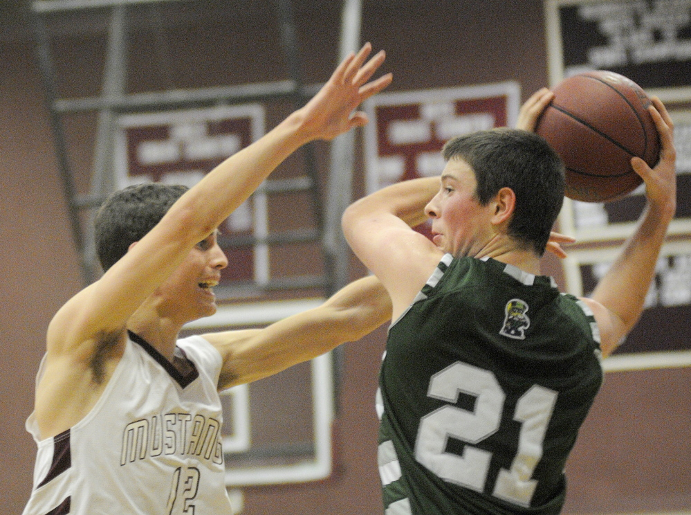 Staff photo by Andy Molloy OPEN ARMS: Monmouth Academy's Brett Wilson, left, attempts to block a pass Thursday by Winthrop High School's Matt Sekerak during a basketball match up in Monmouth.