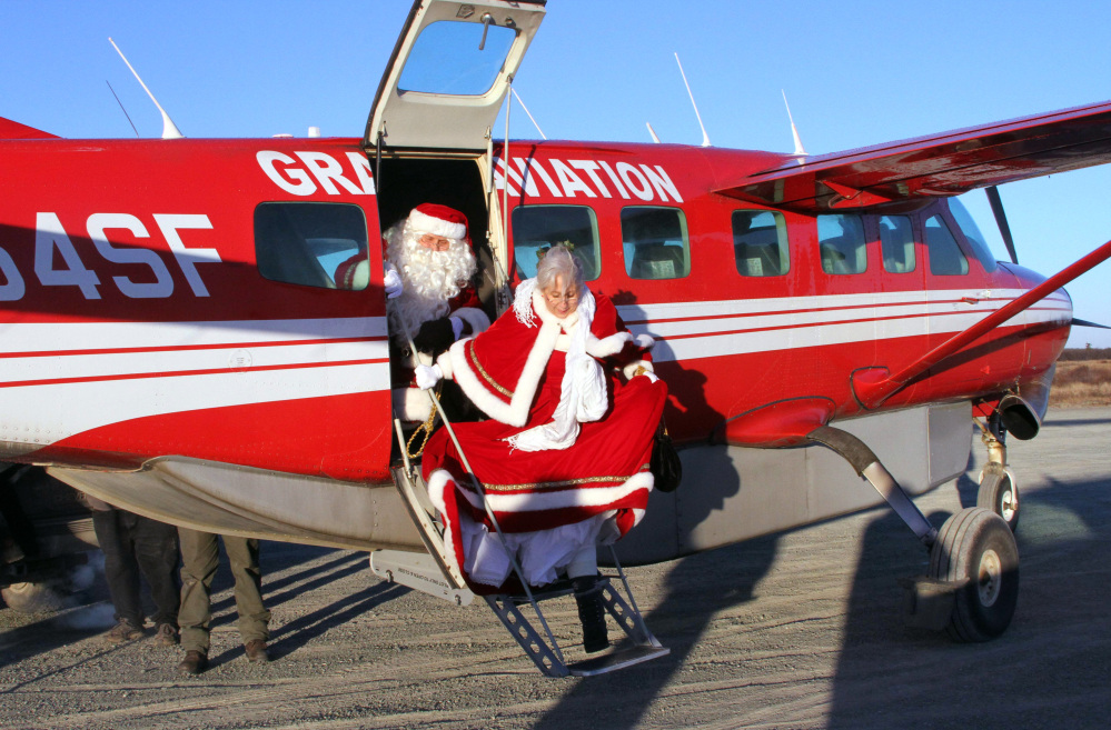 Santa and Mrs. Claus get off a small airplane to visit the children in Kwethluk, Alaska. AP Photo